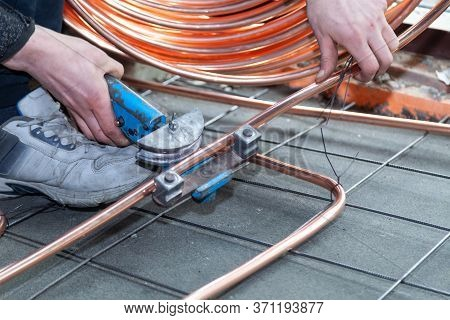 Male Hands Bends Copper Pipes By Pipe Bender