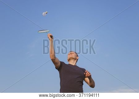 Young Caucasian Man Plays Badminton On A Background Of Blue Sky. The Concept Of An Amateur Game Of B