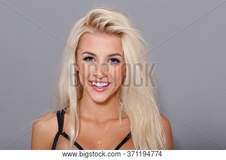 Beauty Frontal Portrait. Sexy Blonde Girl Smiling On Gray Background, Looking At Camera.