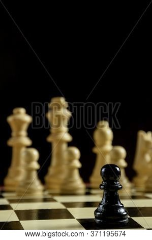 On A Chessboard In The Foreground Is A Black Chess Piece Pawn. Behind Her Are A Row Of White Shapes