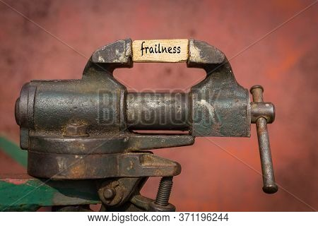 Concept Of Dealing With Problem. Vice Grip Tool Squeezing A Plank With The Word Frailness
