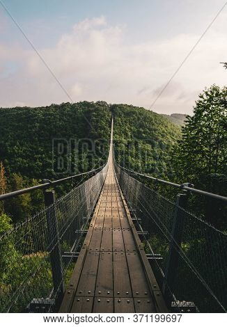 Brown Wooden Hanging Bridge In The Evergreen Tropical Forest Over Top Of Trees For Adventure Walking