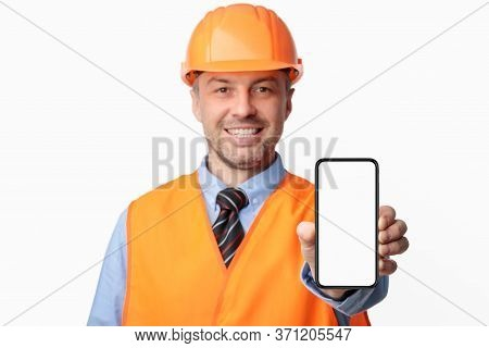Building Services. Construction Worker Showing Cellphone Empty Screen Smiling To Camera Standing On