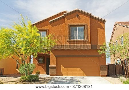 New Two-story, Brown And Burnt Orange Stucco Home In Tucson, Arizona, Usa With Beautiful Blue Sky An