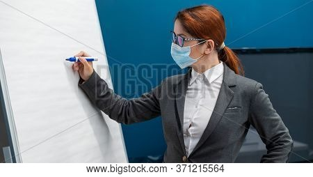 A Woman In A Medical Mask Leads A Seminar In A Conference Hall. Business Coach Writes On A Paper Whi