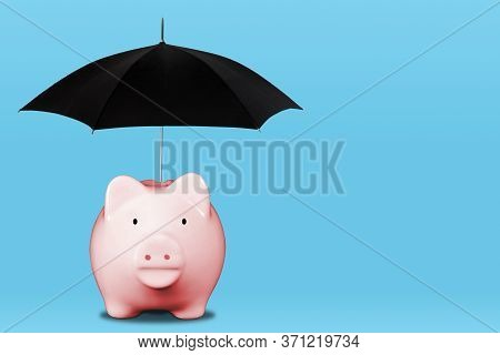 Saving For A Rainy Day With Pink Piggy Bank And Umbrella. Concept Of Financial Security, Savings, In