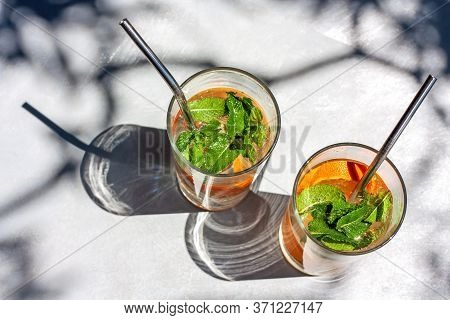 Detox Water Or Orange Cocktail With Slices Of Orange And Mint In Glass With Metal Recyclable Straw.