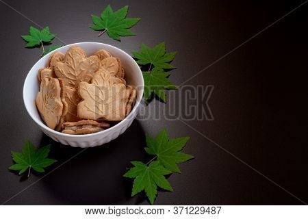 Canadian Cookies In White Ceramic Bowl With Minature Maple Leaves On Dark Background. High Angle Vie