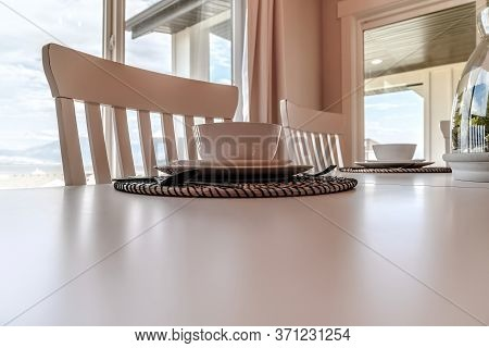 Tableware And Utensils On Woven Placemat At The Dining Table With Chairs