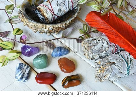 A Close Up Image Of Chakra Healing Crystals With White Sage Smudge Sticks And Orange Sacred Feather.