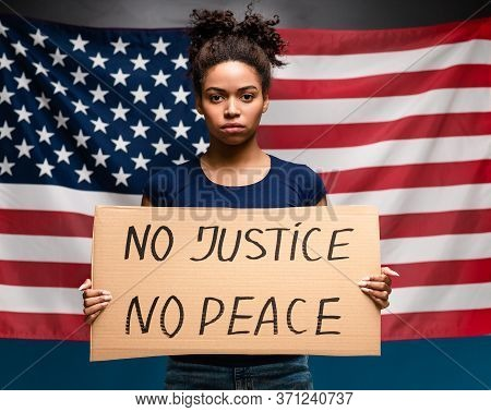 No Peace No Justice. Serious African American Girl Holding Demonstration Placard, American Flag Back