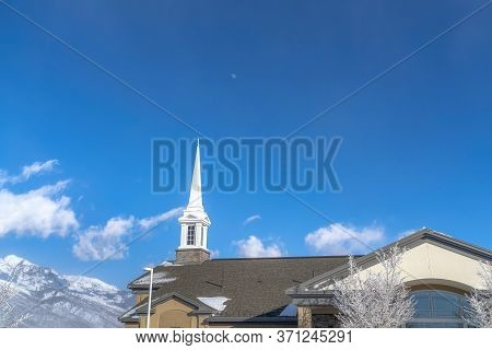Gray Roof And White Steeple Of Church On Winter View Of Snowy Wasatch Mountains