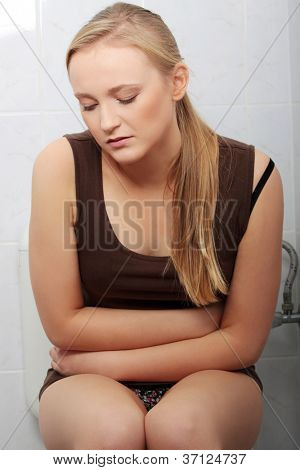 Young casual woman with stomach issues in toilet