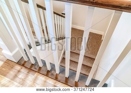 White Wooden Baluster And Brown Handrail Of U Shaped Staircase Inside A Home