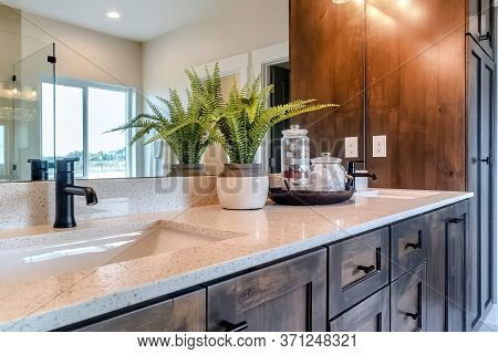 Sink And Faucet Of Bathroom With Wood Cabinets And Window Reflected On Mirror
