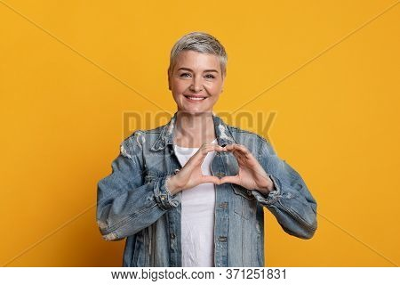 Smiling Kind Mature Woman Shaping Hands Like Heart, Making Love Gesture While Posing On Yellow Backg