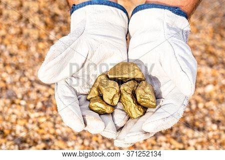 Miner Hand Holding Stones From Another, Gold Mineral Extraction, Precious Stone Exploration Concept.