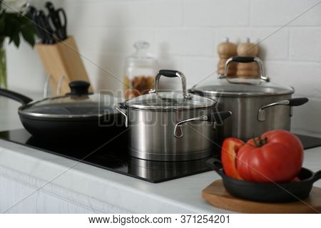 Saucepots And Frying Pan On Induction Stove In Kitchen