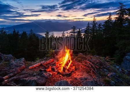 Warm Camp Fire On Top Of A Mountain With Beautiful Canadian Nature Landscape In Background During A