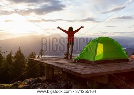 Adventure Girl And Camping Tent On Top Of A Mountain With Canadian Nature Landscape In The Backgroun