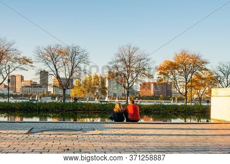 Boston, Usa - October 13 2014; Couple Sit On Esplanade Beside Storrow Lagoon In Late Afternoon Sun O