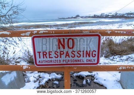 Close Up Of No Trespassing Signage With Snowy Utah Lake Background In Winter