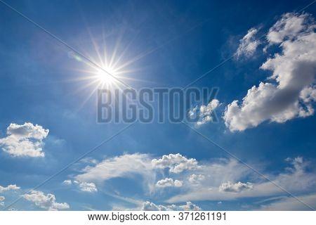 Shining Sun On Clear Blue Sky. Lens Flare Of Sunlight On Blue Sky Background. Bright Sun On Blue Sky