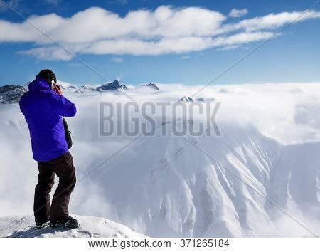 Skier In Blue Jacket At Top Of Mount Talking On Mobile Phone And Snowy Mountains In Fog. Caucasus Mo