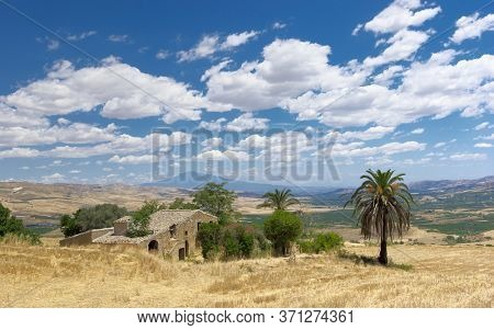 sunny Sicily landscape of countryside with rural farm house, palme tree, Etna Mount on background below cloudscape