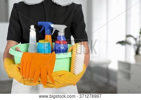 Young Chambermaid Holding Plastic Basin With Detergents In Office, Closeup