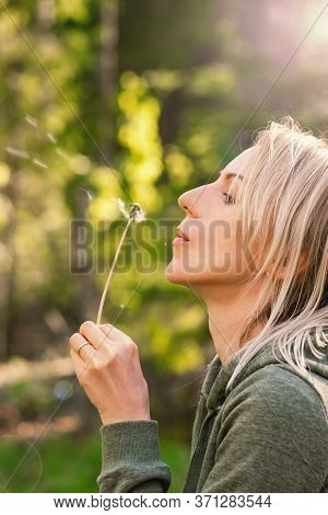 Blonde Woman Blowing Dandelion Blossom Fluffs In The Background Of Blurred Dense Green Forest During
