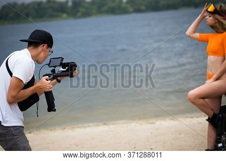 Young Guy Cameraman Shoots A Model On Camera. Shooting Video Content. Backstage.