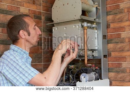 Gas Boiler Maintenance, Man Disassembles A Gas Boiler To Unscrew The Bolt In The Combustion Chamber