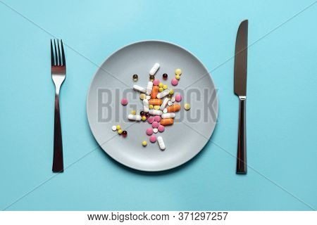 A Handful Of Pills, Capsules And Multi-colored Tablets On A Plate Next To Cutlery. Taking Medication