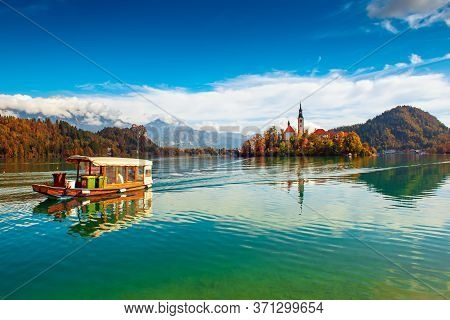 Church Of Assumption In Lake Bled, Slovenia With Blue Sky, Touristic Boat And Clouds In The Autumn
