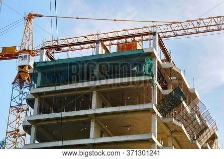 Concrete Building Under Construction. Construction Site. Self-erection Crane Near Concrete Building.