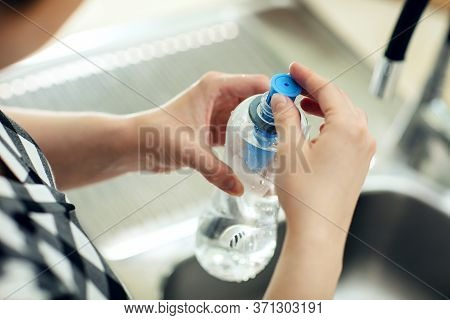 Putting The Carbon Filter Into The Bottle. Woman Puts Carbon Filter Into The Reusable Bottle With Fr