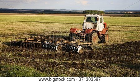 Tractor Plows And Harrows Land In Large Field On Sunny Spring Day. Preparing Soil For Planting Crops