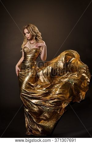 Dancing Woman In Gold Dress Flying On Wind, Beautiful Lady In Fluttering Sparkling Golden Gown