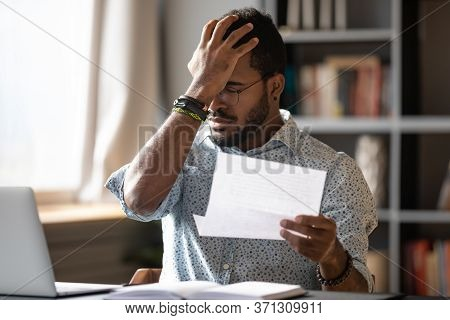African Businessman Holding Letter Reading Bad Bank News About Debt