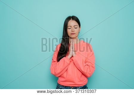 Peaceful Young Beautiful Female Dressed In Casual, Keeps Hands In Praying Gesture, Has Calm Expressi