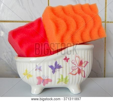 Red And Orange Sponges In A Special Stand For Sponges With Butterflies