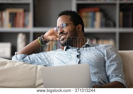 African Guy Distracted From Using Laptop Daydreams Looking At Window