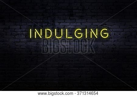 Neon Sign On Brick Wall At Night. Inscription Indulging