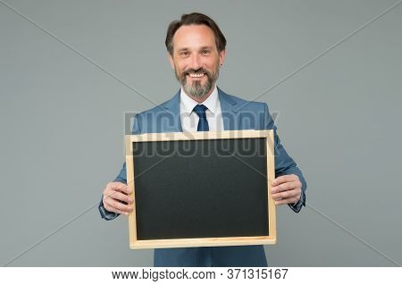 Publicity And Education Measures. Happy Manager Hold Blackboard Grey Background. Bearded Man Smile W
