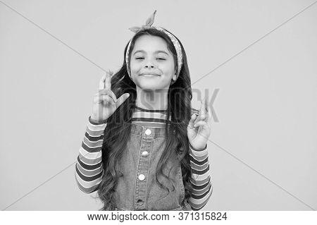 Little Girl Praying. Retro Girl Crossed Fingers. Please. Wait Impatiently. Little Child Yellow Wall.