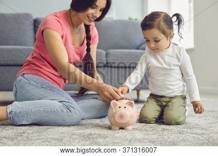 Young Mother And Her Daughter Putting Coins Into Piggy Bank At Home. Parent Giving Child Financial E