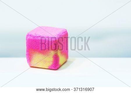 Salt Bath Bomb. Pink And Yellow Cube Of Bath Salt Lies On The Bath