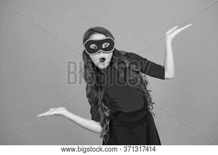 Masquerade Concept. Kid Wear Eye Mask. Girl Wear Mask Orange Background. Event And Entertainment. Pa