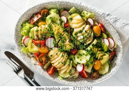 Summer Fresh Salad Of Fruits And Vegetables In An Oval Plate On A Table With Cutlery. Healthly Food